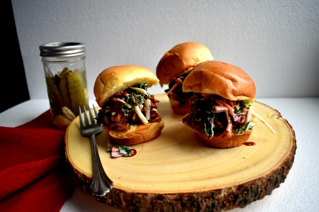 Sweet crusted cola shredded pork sliders topped with crunchy kale apple slaw and pickled jalapenos