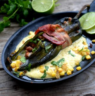 Stuffed poblano wrapped in bacon in cream corn sauce