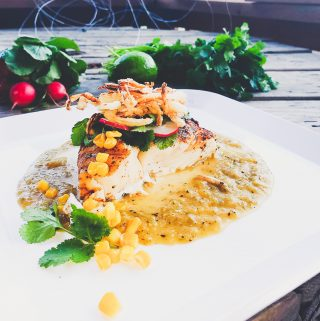 Halibut in roasted tomatillo sauce with crispy fried onions
