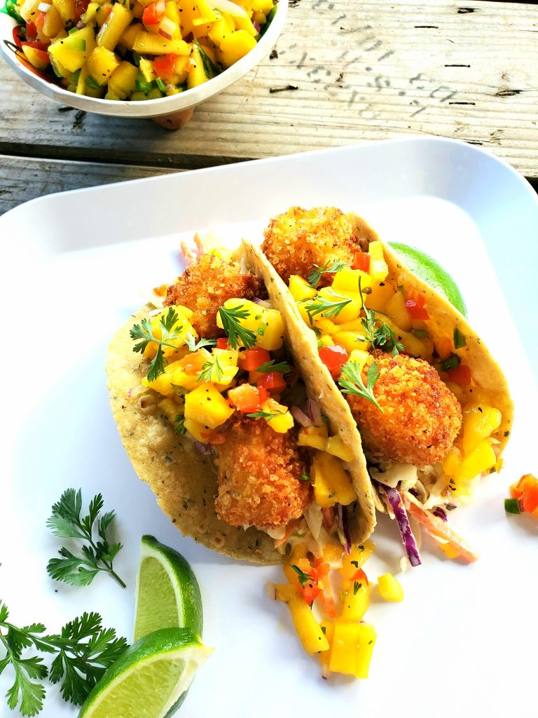Crunchy Fish Tacos combines bite size Panko coated cod cubes with sweet mango salsa and a creamy, smoky angle hair coleslaw.