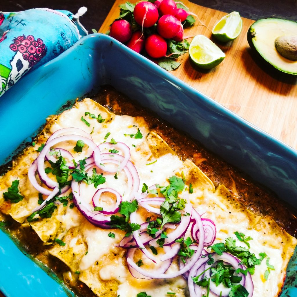 Creamy, cheesy Enchiladas Suiza uses a tomatillo base and is topped with thinly sliced red onion and cilantro