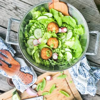 Lightly fried goat cheese medallions sit ever so delicately on this inviting summer salad with fresh, seasonal greens layered with cucumber, radish and garden peas.