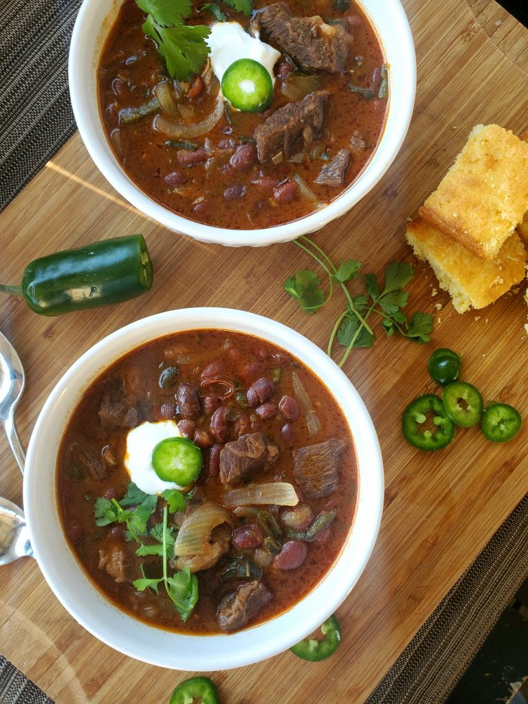 Tender steak, pinto beans and poblano chili peppers come together with a splash of liquid smoke for a hearty bowl of chili.  Topped with sour cream, cilantro and sliced jalapenos.