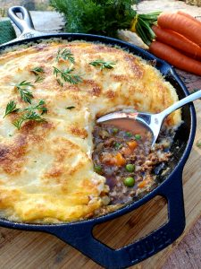 Classic Cottage Pie is made with spiced ground beef, tender carrots and peas. Topped with creamy potato cheese mixture and carrot tops.