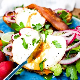 Avocado Breakfast Molette is a Mexican inspired avocado toast with layers of pinto beans, smashed avocado, pickled onions, Cotija cheese, cilantro and a fried egg on a bolillo roll.
