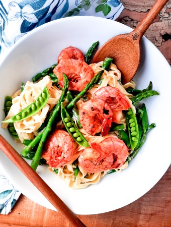 Creamy Spring Pasta with Shrimp combines first of the season asparagus and peas in a cream based sauce with tender garlic shrimp.