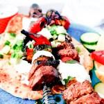 Tender, marinated Greek Inspired Steak Kabobs with Tzatziki, zucchini, mushroom, chili peppers and cucumber dill relish top pita bread.